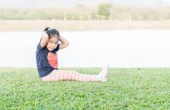 Esercizio asiatico sveglio della ragazza su erba verde Immagine Stock