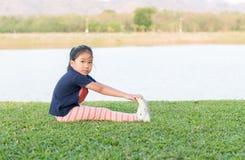 Esercizio asiatico sveglio della ragazza su erba verde Immagini Stock Libere da Diritti