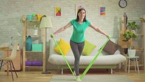 Esercizio atletico della ragazza con il indor delle bande di resistenza video d archivio