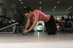 Esercizio attraente della donna con il rullo della ruota per l'ABS Immagini Stock Libere da Diritti