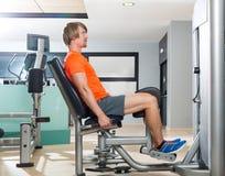 Esercizio biondo dell'uomo di abduzione dell'anca al closing della palestra Fotografia Stock