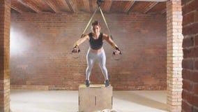 Esercizio con le cinghie d'attaccatura Trx ragazza impegnata negli sport stretti in palestra sul trx della cinghia archivi video