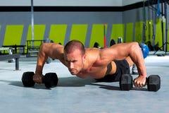 Esercizio del pushup di forza di flessione dell'uomo della palestra con il dumbbell Fotografie Stock
