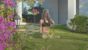 Esercizio del respiro di yoga di Pranayama da una giovane donna nel cortile della sua casa stock footage