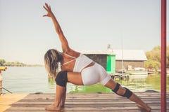 Esercizio dell'istruttore di forma fisica della donna all'aperto sulla zattera di legno del fiume Fotografia Stock