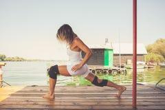 Esercizio dell'istruttore di forma fisica della donna all'aperto sulla zattera di legno del fiume Fotografie Stock