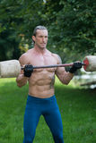 Esercizio dell'uomo con l'allenamento fatto del bilanciere della mano all'aperto Fotografia Stock Libera da Diritti