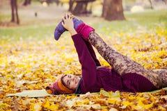 Esercizio della donna che allunga nel parco di autunno Immagine Stock Libera da Diritti