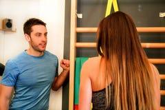 Esercizio della donna con aiuto del suo istruttore di forma fisica in palestra Immagine Stock