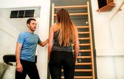Esercizio della donna con aiuto del suo istruttore di forma fisica in palestra Immagini Stock