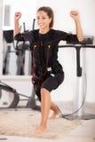 Esercizio della giovane donna sull'elettro macchina di stimolazione Immagine Stock Libera da Diritti