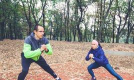 Esercizio delle coppie di forma fisica nella mattina ad Autumn Park immagini stock libere da diritti
