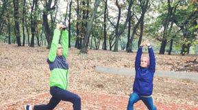 Esercizio delle coppie di forma fisica nella mattina ad Autumn Park fotografie stock