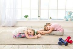 Esercizio delle sorelle delle ragazze dei bambini insieme all'interno Fotografie Stock Libere da Diritti