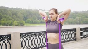 Esercizio di allenamento della ragazza di forma fisica con la banda di resistenza durante l'allenamento all'aperto stock footage