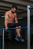 Esercizio di Doing Heavy Weight dell'atleta sulle parallele simmetriche Fotografia Stock