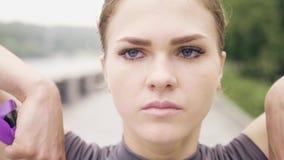 Esercizio di forma fisica di addestramento della giovane donna del fronte con la fine dell'estensore di resistenza su stock footage