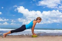 Esercizio di forma fisica della donna con la noce di cocco cruda sulla spiaggia dell'oceano Fotografia Stock Libera da Diritti