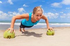 Esercizio di forma fisica della donna con le noci di cocco verdi sulla spiaggia dell'oceano Immagini Stock Libere da Diritti