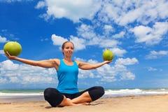 Esercizio di forma fisica della donna con le noci di cocco verdi sulla spiaggia dell'oceano Fotografia Stock