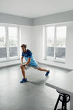 Esercizio di forma fisica Uomo che allunga scaldandosi corpo prima della formazione Immagini Stock Libere da Diritti