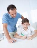 Esercizio di Helping Boy With dell'insegnante fotografia stock libera da diritti