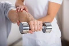 Esercizio di Helping Man To del fisioterapista fotografia stock