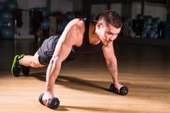 Esercizio di piegamento sulle braccia di forza di flessione dell'uomo della palestra con la testa di legno in un allenamento di f Immagini Stock Libere da Diritti