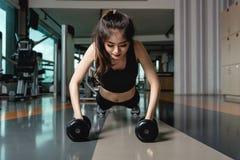 Esercizio di piegamento sulle braccia di forza di flessione di allenamento della giovane donna della palestra con il du Immagini Stock Libere da Diritti