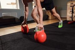 Esercizio di piegamento sulle braccia di forza di flessione dell'uomo della palestra con Kettlebell in un allenamento Fotografie Stock