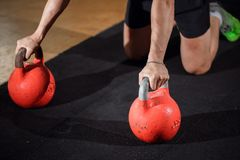 Esercizio di piegamento sulle braccia di forza di flessione dell'uomo della palestra con Kettlebell in un allenamento Immagine Stock Libera da Diritti
