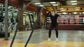 Esercizio di pratica della corda di battaglia della donna atletica durante l'allenamento del crossfit in palestra video d archivio