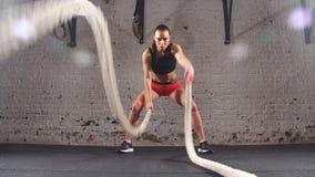 Esercizio di pratica della corda di battaglia della giovane ragazza adulta durante l'allenamento adatto dell'incrocio alla palest archivi video