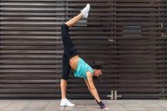 Esercizio di pratica di yoga dell'atleta femminile allungando le sue gambe all'aperto Giovane donna sportiva che fa posa stante d Fotografie Stock