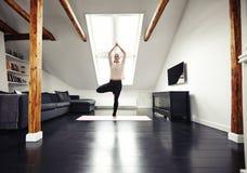Esercizio di pratica di yoga della giovane donna caucasica a casa Fotografia Stock Libera da Diritti