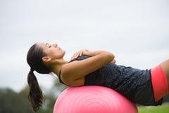 Esercizio di yoga della giovane donna sulla palla di misura Immagine Stock