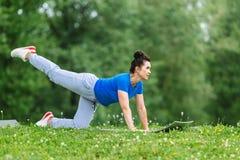 Esercizio facente femminile invecchiato di yoga in parco Outdor di pratica di yoga della donna senior Concetto coperto di erica d Fotografie Stock
