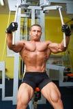 Esercizio a forma di dell'uomo del muscolo sulla palestra di sport Fotografia Stock