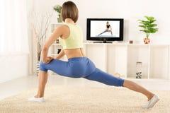 Esercizio grazioso della donna in Front Of TV Fotografie Stock