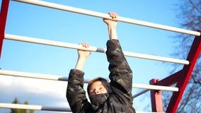 Esercizio nell'aria fresca Giovane forte tipo che fa gli esercizi sulla barra Parco di autunno archivi video