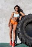 Esercizio sportivo della ragazza con la grande gomma Fotografia Stock Libera da Diritti