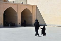 Muslim woman with traditional chador, Iran. ESFAHAN, IRAN - 25 OCTOBER 2018: Muslim mother with the daughter with traditional chador is going along streets in stock photos