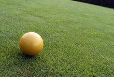 Esfera amarela no campo de golfe Imagens de Stock Royalty Free