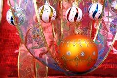 Esfera anaranjada de la Navidad con un modelo y una cinta celebradora 3 Foto de archivo libre de regalías