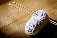 Esfera das lãs e das agulhas de confecção de malhas Foto de Stock