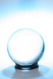 Esfera de cristal cercada por azul Imagens de Stock Royalty Free