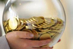 Esfera de cristal con las monedas Imagenes de archivo