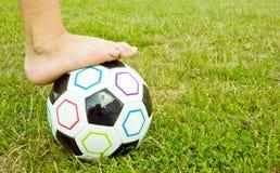 Esfera de futebol com pé dos miúdos nele Fotografia de Stock Royalty Free