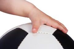 Esfera de futebol da preensão da mão do bebê foto de stock