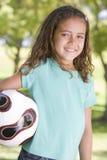 Esfera de futebol da terra arrendada da rapariga que sorri ao ar livre Fotografia de Stock Royalty Free